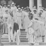 C.P. Iaukea holding Queen Liliuokalani's Red Cross Flag on steps of Iolani Palace while Gov. Pinkham speaks
